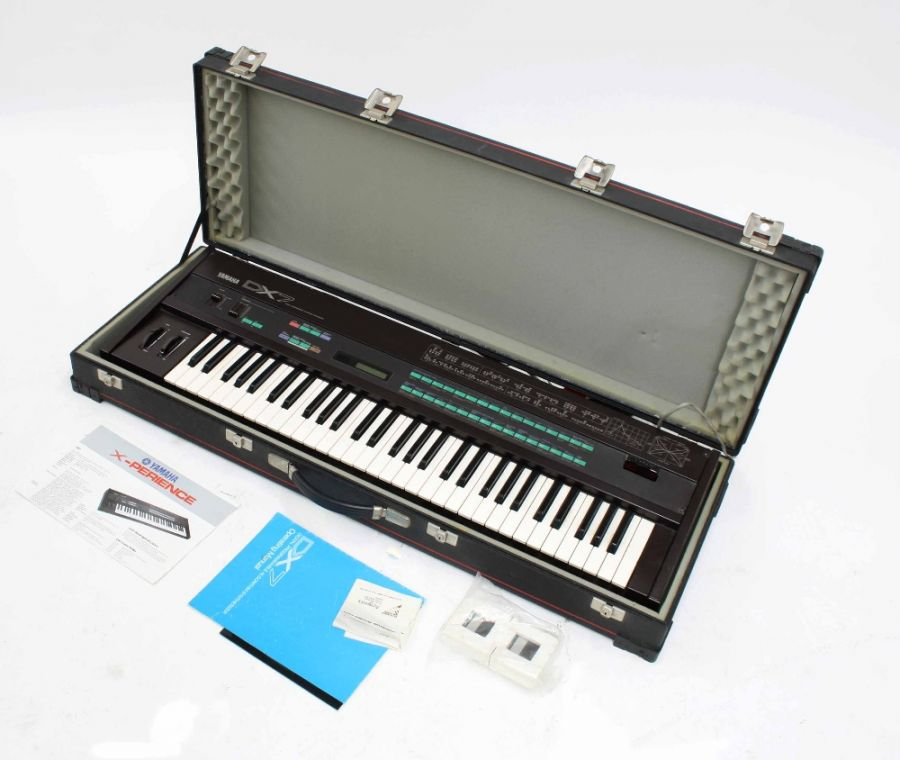 Lot Number 949. Yamaha DX7 Mark 1 synthesizer keyboard, made in Japan, ser. no. 121953, sold with EX1024 Hypra-Rom, two further data cartridges, music ledge, Yamaha foot pedal and operating manual, within a flight case. Auctioned at Entertainment Memorabilia, Guitar Amps & Effects on 12th March 2020