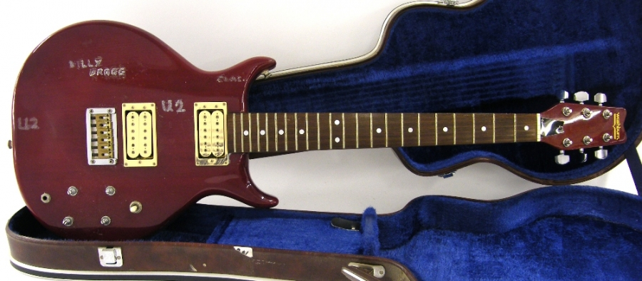 Lot Number 66. 1980s Washburn Wing Series Raven electric guitar, made in Japan, ser. no GG810188, red finish with heavy wear, also defaced with writing to the front, missing control knobs, electrics appear to be in working order, hard case, condition: poor. Auctioned at The Guitar Auction - Including The Geoff Banks Collection on 16th March 2017