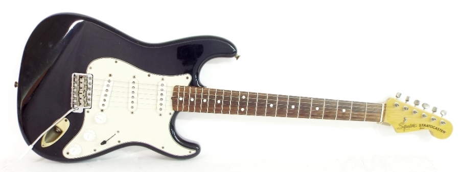 Lot Number 176. 1983 Squier by Fender Stratocaster electric guitar, probably JV series, black finish with heavy wear in places including significant finish loss, wear to frets, replaced backplate and jack plate, electrics in working order, condition: fair. Auctioned at The Guitar Auction on 8th December 2016