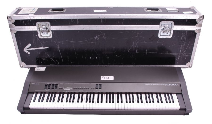 Lot Number 187. *Gary Moore - Roland RD-300S digital piano, made in Japan, ser. no. AC22021, fitted within a flight case on wheels (110 volts only) *Bought in the USA for the start of the sessions that would become the 'After Hours' album and was used by the late Tommy Eyre extensively on tour for the 'After Hours', 'Live blues', 'BBM' and 'Blues for Greeny' tours. It can be seen and heard on various live videos and albums between 1992 - 1995 **This lot is subject to VAT of 20% on the hammer price  ?250-500. Auctioned at The Guitar Auction - Including The Gary Moore Collection on 11th December 2019